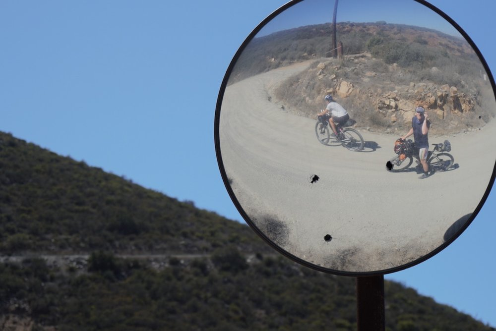 Reflection of Caitlin and Devon climbing hill in Baja